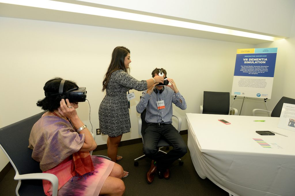 Attendees of CABHI's Innovation Showcase try the VR Dementia Simulation project.