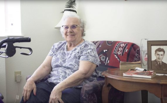 Older woman seated on couch surrounded by family photos smiles; walker is parked nearby