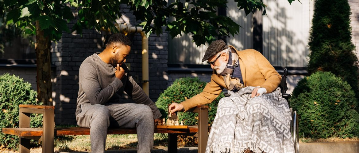 young man playing chess with older adult man in a park