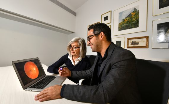 CEO Eliav Shaked shows the RetiSpec technology to an older adult