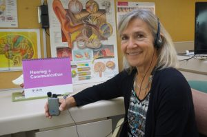 Audiologist Marilyn Reed hold an amplification device in her office
