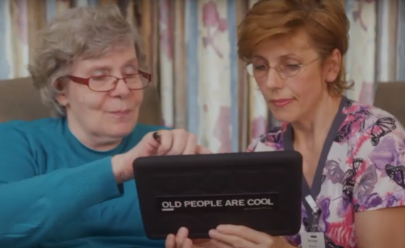 Older adult woman and a female nurse look at a tablet together.