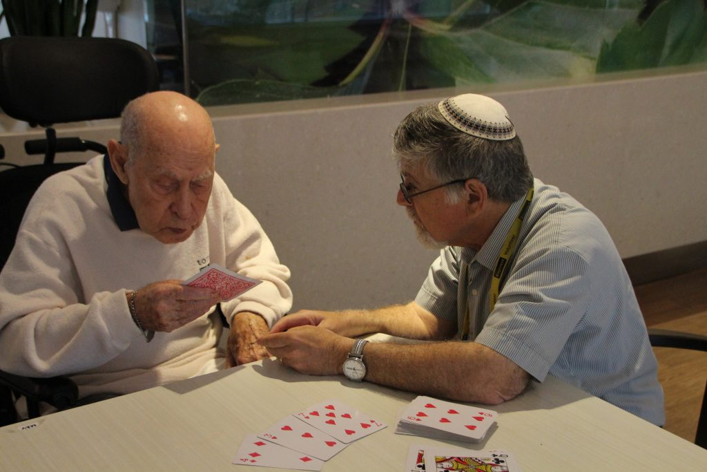 A volunteer plays cards with a Baycrest resident during a PLEASE Program session.