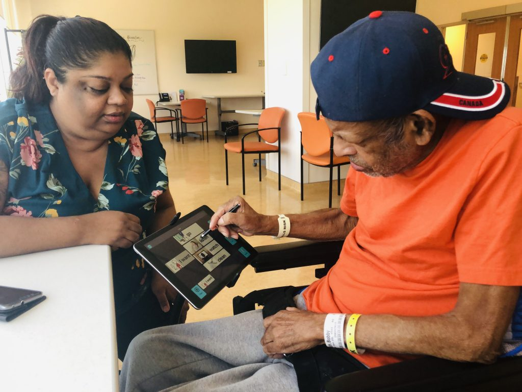 Older male adult uses the Linggo app with a family member