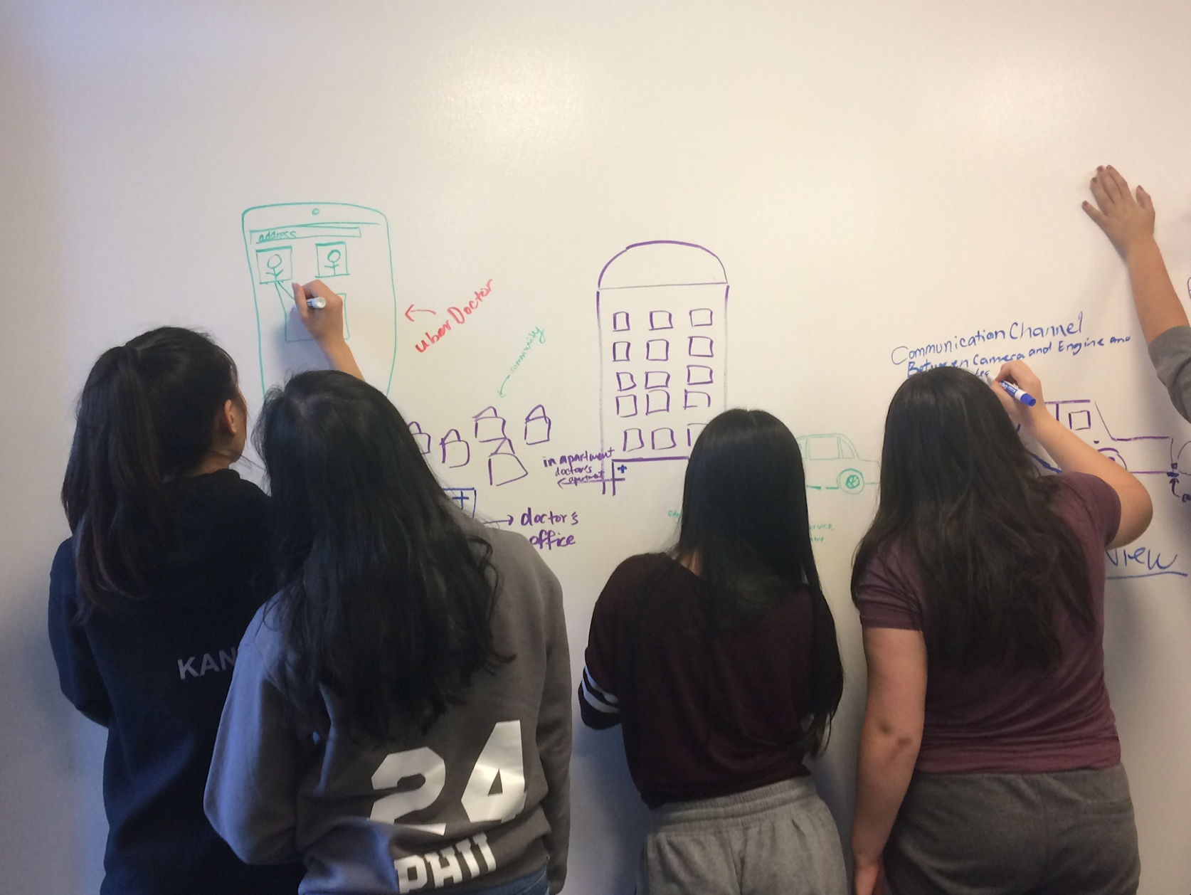 Students draw on the white board during a CABHI-hosted workshop to brainstorm innovations.