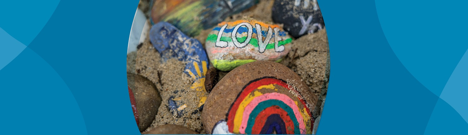 Rocks painted with rainbows and the word love