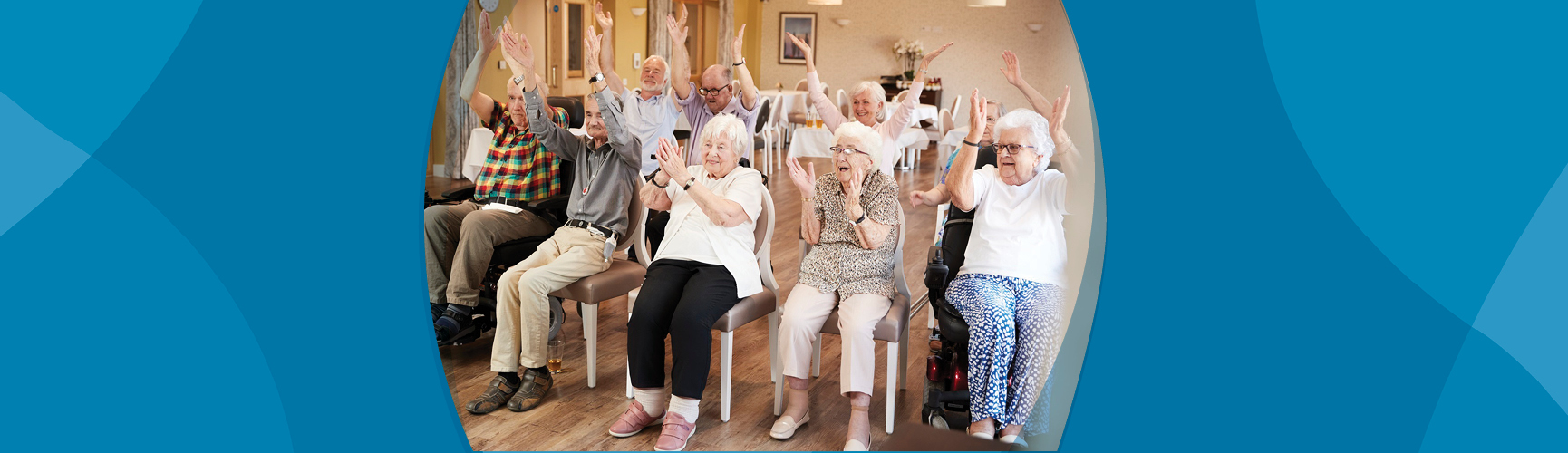 Group of older adults sitting in chairs with arms raised