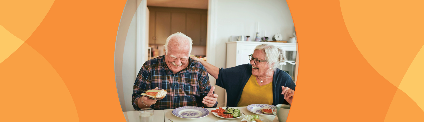Man and woman sitting and eating at a table while laughing