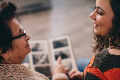 Older adult woman and young woman look through photo album.