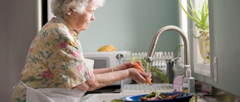 Older adult woman washing vegetables at her kitchen sink.