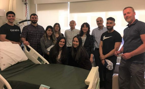 11 people standing around a hospital bed smiling.