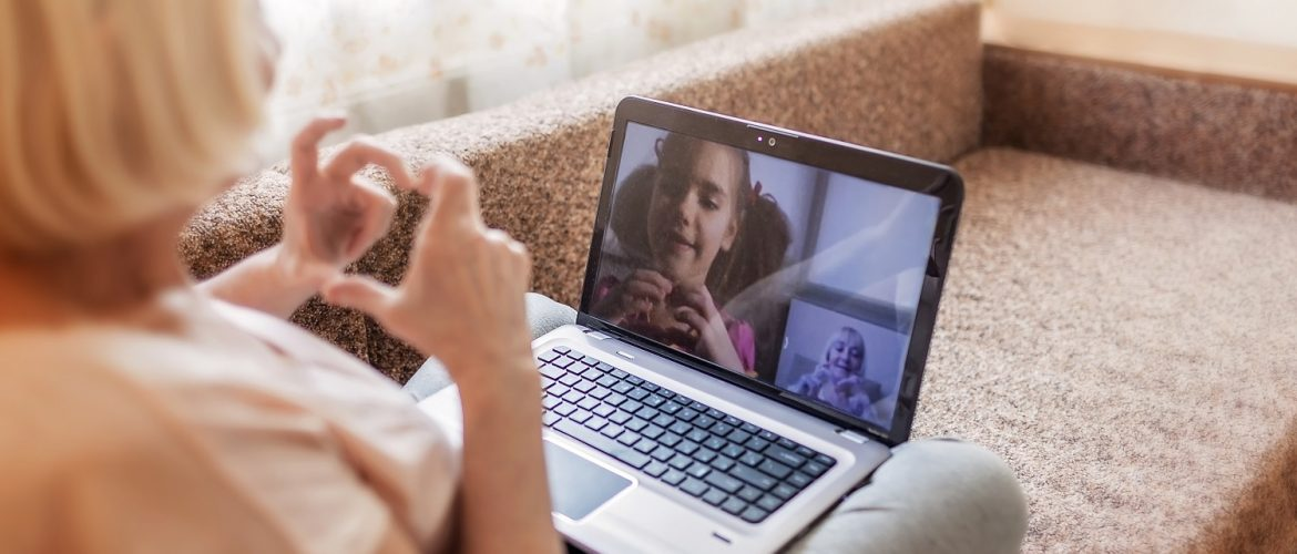 Older adult woman on a video conference call with a little girl.