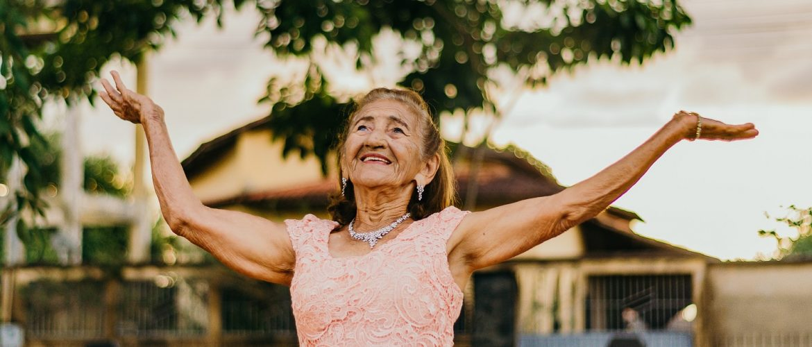 Older adult woman smiling with her arms raised in the air.