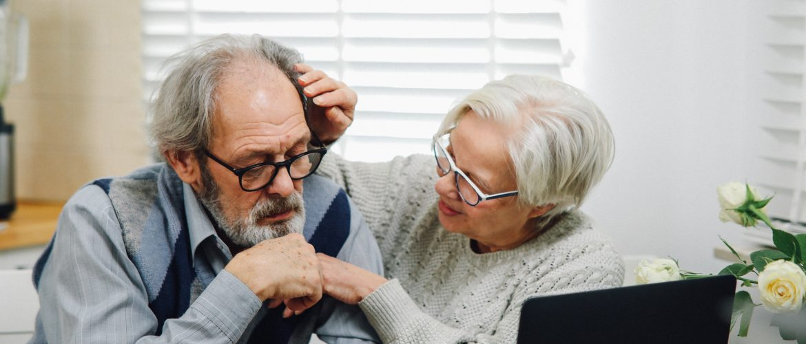 Woman touching the forehead of an older adult man