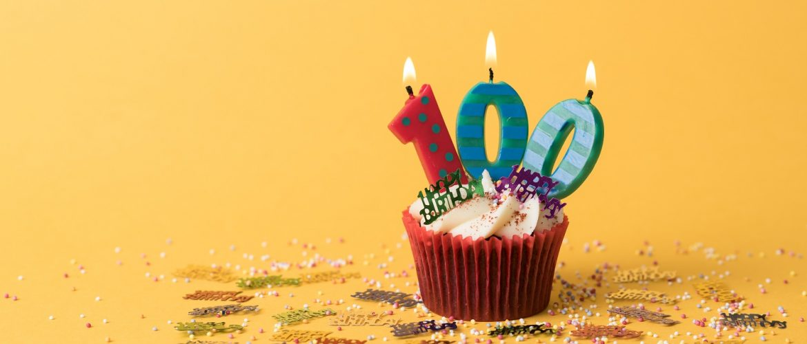 A cupcake with birthday candles spelling out 100.