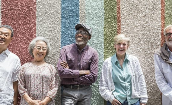 A group of diverse seniors stand up against a multi-coloured wall